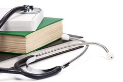 Pile of books and stethoscope isolated on white Stock Photos