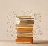A pile of books on table with school hand drawn doodle sketches Stock Photos