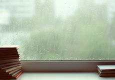 Pile of books before a window. Behind a window it is raining. The Flavovirent shade Stock Photos