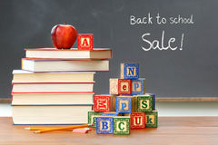 Pile of books with wooden blocks. In front of chalkboard royalty free stock photo