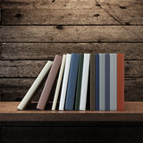 Pile of books on wooden shelf Royalty Free Stock Photo