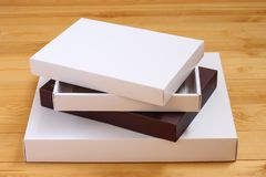 Pile of boxes in colored paper on wooden background stock images