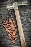 Pile of brass nails claw hammer on wooden board.  Royalty Free Stock Image