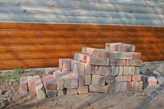 PILE OF BRICKS NEXT TO WOODEN CHALET stock images