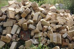 Pile of bricks by an old brick wall taken by an old building in on one of the city streets.  stock image