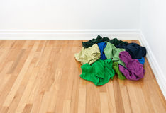 Pile of bright clothes in the room corner. Pile of bright colorful clothes on the floor in the corner of the room Royalty Free Stock Photos