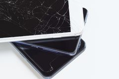 A pile of broken mobile phone on white background. Repair or disposal stock image