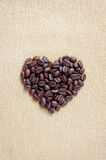 Pile of brown coffee beans in heart shape. Close up of coffee beans on background or texture of sack cloth stock image