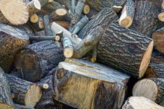 A pile of brown firewood and logs in the yard. Texture of a pile of brown firewood and logs in the yard Stock Image
