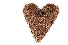 A pile of brown flax seeds in heart shape form on  white background Royalty Free Stock Photos