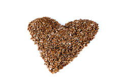 A pile of brown flax seeds in heart shape form on  white background. Royalty Free Stock Photo