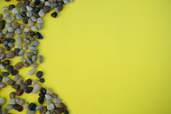 A pile of brown pebbles on yellow background royalty free stock images