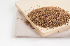 Pile of buckwheat seeds on the board. Pile of buckwheat seeds on the wooden board Royalty Free Stock Photo