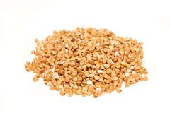 Pile of buckwheat seeds on the white background. Pile of buckwheat seeds isolated on the white background Stock Image
