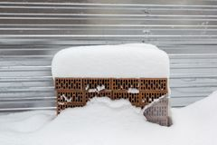 Pile of building bricks in the winter under the snow. Construction background royalty free stock image