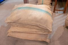Pile of burlap sacks with green stripe on concrete floor royalty free stock photos