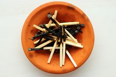 Pile of burnt matches in orange clay plate on white background top view. Stock Image