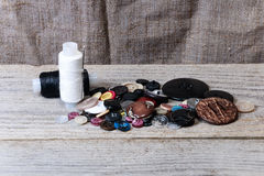 Pile of buttons, black and white thread, needle Royalty Free Stock Photos