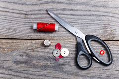 Pile of buttons, scissors, thimble, bobbin of thread. On an old table Stock Photography