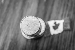 Pile of Canadian one dollar coins with Canadian Flag stock photos
