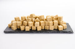 Pile of cane sucar cubes on rectangular dark shale plate Stock Photos
