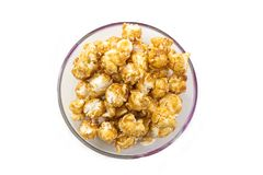 A pile of caramel corn in a bowl on a white background stock photo