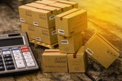 Pile of cardboard boxes products on wood pallet with calculator. Ideas for assembling a portfolio of assets which are held directly by investors. which stock photo