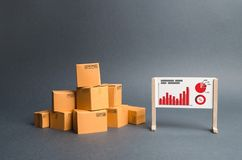 A pile of cardboard boxes and a stand with information and statistical graphs. report on the rate of production and sale of goods royalty free stock photography