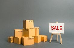 A pile of cardboard boxes and stand with the word sale. sale of products, discounts on goods of the outgoing season. commodity stock photography