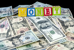 Toy blocks spell the word money on money Stock Photos