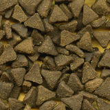 Pile of cat biscuits. Background of triangular brown cat biscuits with yellow background Royalty Free Stock Photos