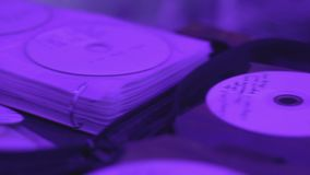 Pile of cd records lying on table, dj performing for audience, party atmosphere