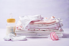 Pile of childrens clothing with a bottle of milk and pacifier. Close-up Stock Photos