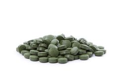 Chlorella tablets. A pile of Chlorella pills. Isolated on white. These tablets are for animals Stock Image