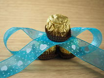 Pile of chocolate balls, decorated blue sky ribbon Stock Image