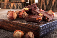 Pile of chocolate bars with nuts. Pile of delicious chocolate bars with whole nuts on wood, Warm composition of chocolate pieces with hazelnuts Stock Photography