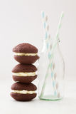 Pile of chocolate whoopie cakes with milk bottle Royalty Free Stock Images