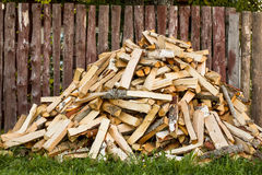 Pile of chopped firewood. Lies near the fence at the house Royalty Free Stock Photography