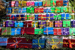 Pile of Christmas gifts. A shower of gifts, colorfully plastic wrapped and piled outside in a park Royalty Free Stock Photos