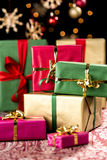Pile of Christmas Gifts. Stack of plain presents in red, green and gold placed on a festive cloth. Orange light reflexes, blurred stars and baubles in the back Stock Photos