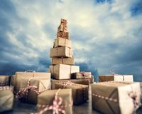 Pile of Christmas gifts wrapped in brown paper against the clou stock images