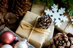 Pile of Christmas and New Year Gift Boxes Wrapped in Craft Paper Colorful Balls Big and Small Pine Cones Green Fir Tree Branches stock images