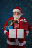 Pile of Christmas presents. Santa Claus holding a pile of Christmas presents Stock Photography