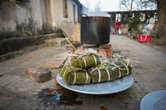 Pile of Chung cakes, Cooked square glutinous rice cake, Vietnamese new year food. Cooking pot on background.  royalty free stock image