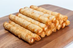 Pile of cigar shaped bakery rolls on wood board. Pile of crunchy baked cigar shaped bakery rolls on wood board on white background stock image