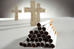 Pile of cigarettes, three crosses in background Stock Images