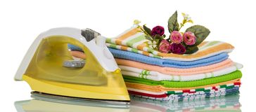 Pile of clean ironed linen and electric iron,  on white Royalty Free Stock Photography