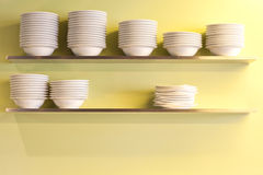 Pile clean side plates on green wall Royalty Free Stock Photos