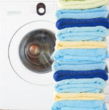 Pile of clean towels with washing machine Royalty Free Stock Photo
