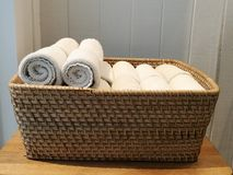 Pile of cloth, hand towel, table napkin, handkerchief on the basket in spa, bath room, toliet with blur white wooden wall backgrou. Nd, sideview stock image